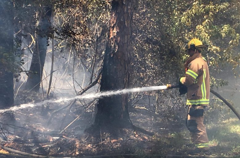 Evacuation lifted; brush fire out, officials say